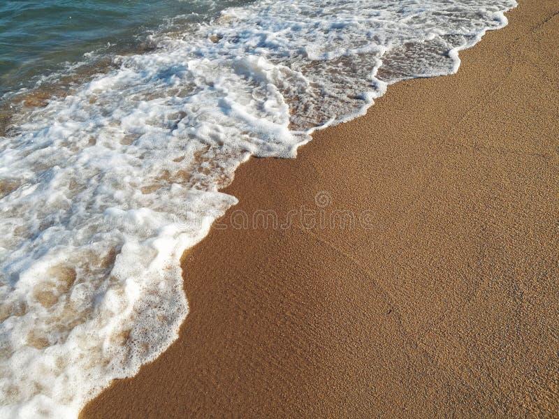 Close-up van de golf die het zandige strand bespatten royalty-vrije stock afbeeldingen