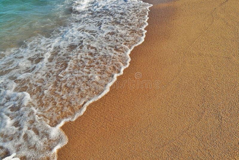 Close-up van de golf die het zandige strand bespatten royalty-vrije stock fotografie