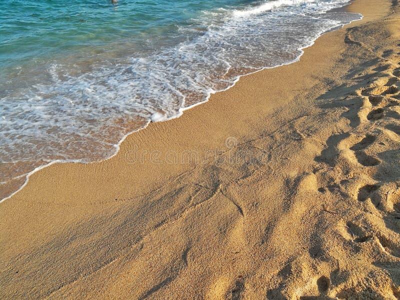 Close-up van de golf die het zandige strand bespatten stock afbeeldingen