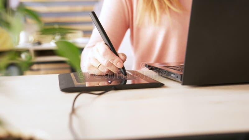 Close-up van de hand die van de vrouwelijke grafische ontwerper interactieve penvertoning, digitale tekeningstablet en pen op een stock foto