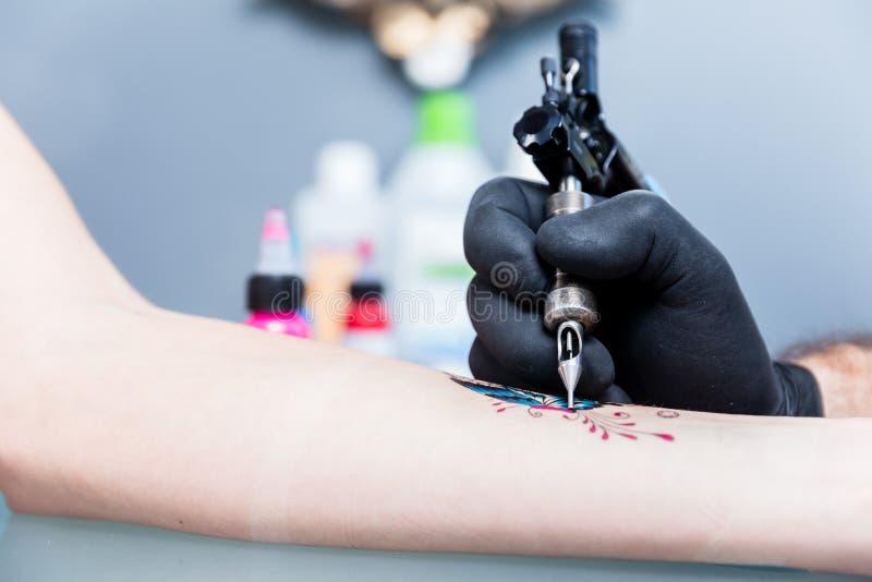 Close-up van de hand van een tatoegeringskunstenaar die een kleurrijke vlinder in de schaduw stellen stock afbeeldingen