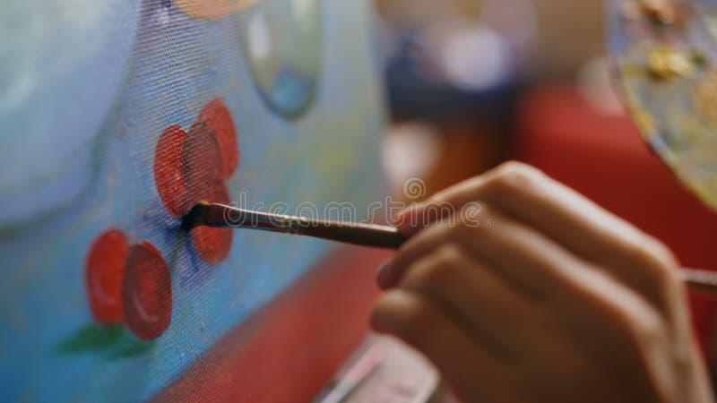 Close-up van de hand van de kunstenaarsvrouw ` s met borstel het schilderen stillevenbeeld op canvas in kunststudio royalty-vrije stock afbeelding