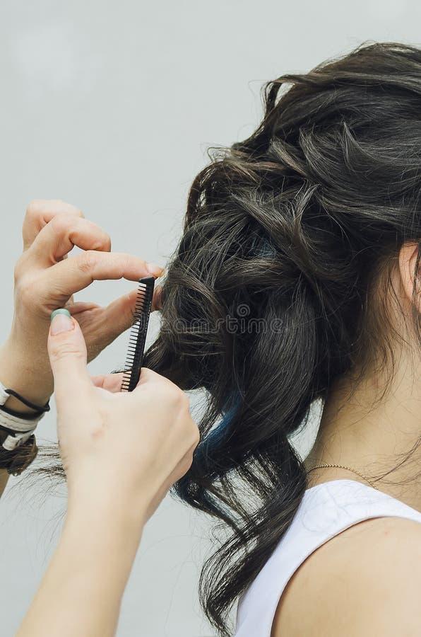 Close-up van de handen die van een professionele kapper een kapsel in een schoonheidssalon doen Model van een brunette met lang h stock fotografie