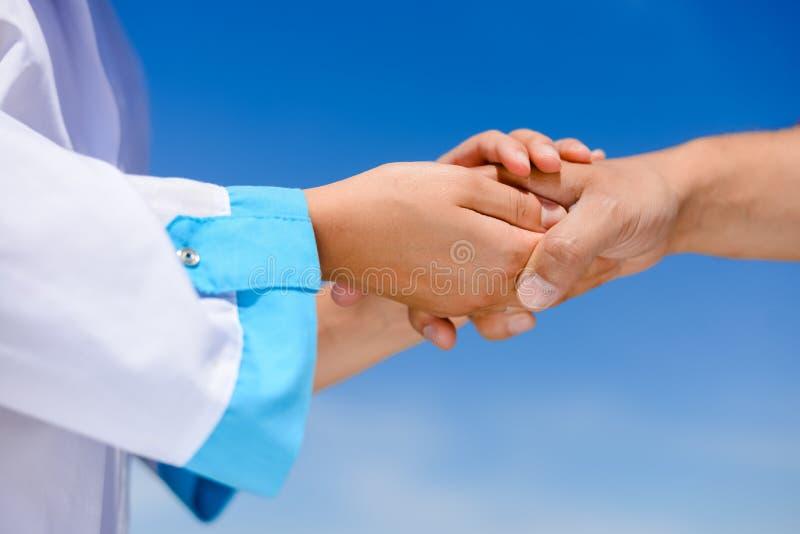 Close-up van de handen die van de geneeskundeverpleegster iemand houden royalty-vrije stock fotografie