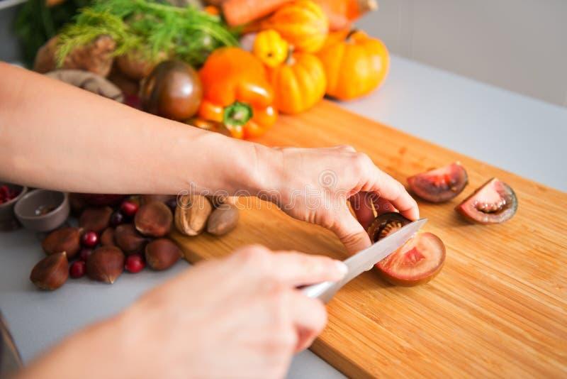 Close-up van de handen die van de vrouw en tomaat houden snijden royalty-vrije stock afbeelding