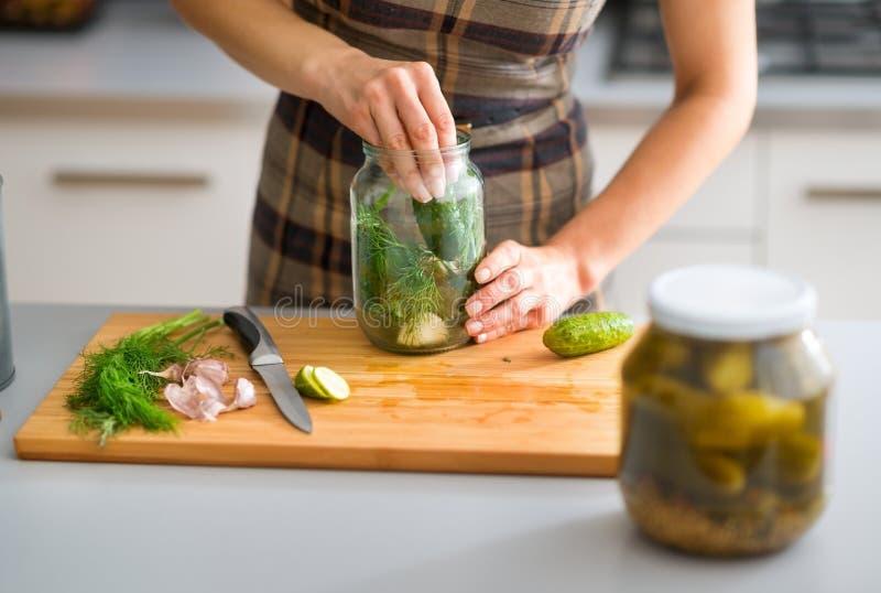 Close-up van de handen die van de vrouw komkommers voor dillegroenten in het zuur voorbereiden stock fotografie