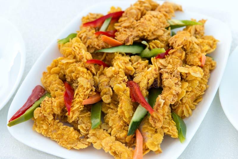 Close-up van de heerlijke knapperige gebraden stroken van de kippenborst op witte plaat, op een witte lijst met peper, gemakkelij stock afbeelding