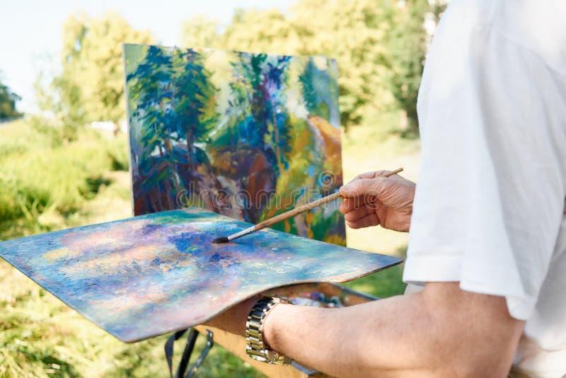 Close-up van de holding van de kunstenaarshand het schilderen borstel en palet van kleuren stock foto's