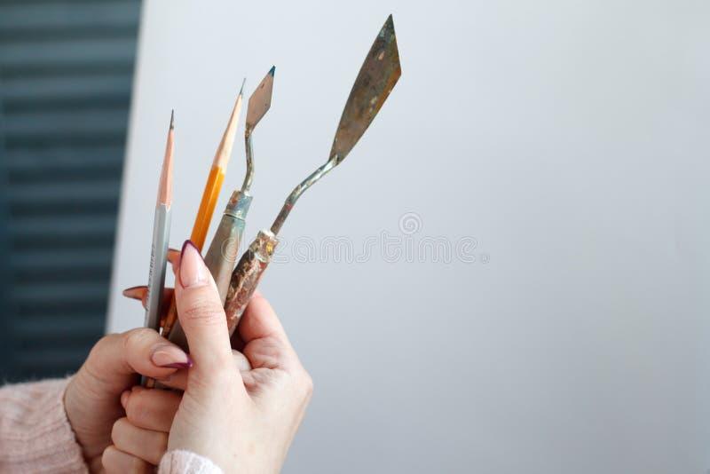 Close-up van de hulpmiddelen van de de handholding van de vrouw om met olie, borstels en spatel, tegen een wit canvas te schilder stock fotografie