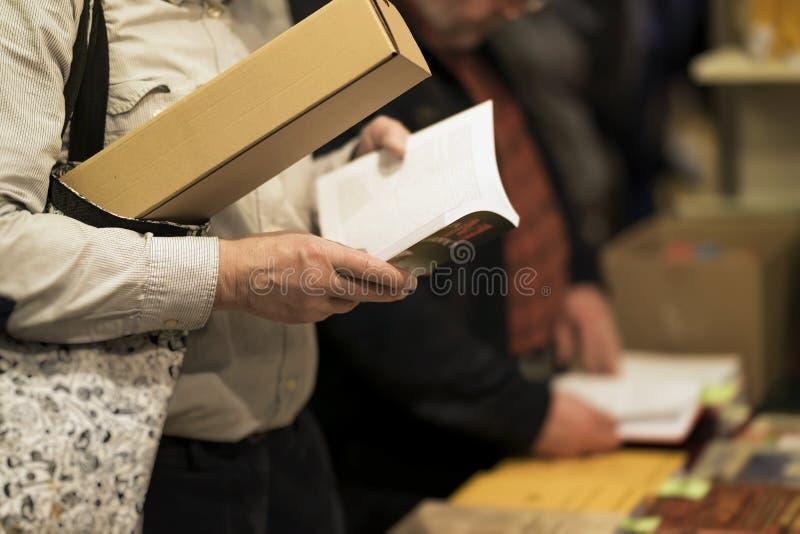Close-up van de mens met zak en open interessant boek, boekhandel Onderwijs, school die, studie, fictieconcept lezen Echt stock afbeeldingen