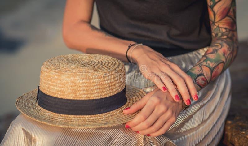 Close-up van de rust van een strohoed op zijn knieën De vrouwelijke hand met tatoegeringen verbetert armbanden De moderne vrouw royalty-vrije stock afbeeldingen