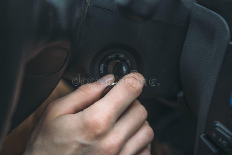 Close-up van de sleutel van de handtussenvoegsels van de mensenbestuurder in ontstekingsslot stock afbeeldingen
