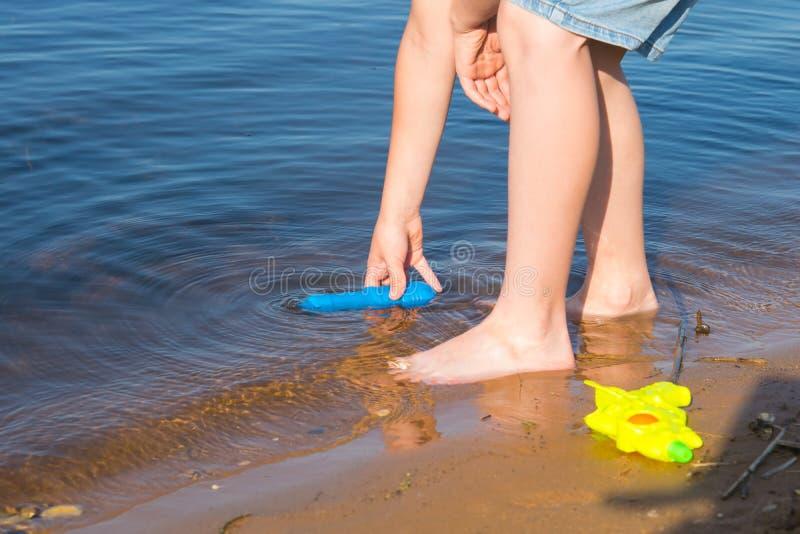 Close-up van de voeten van een jongen die water in een pistool tegen de achtergrond van een meer om neemt te spelen stock fotografie