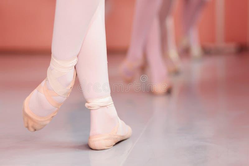 Close-up van de voeten van de tienerballerina, het praktizeren balletbewegingen in een dansende studio royalty-vrije stock fotografie
