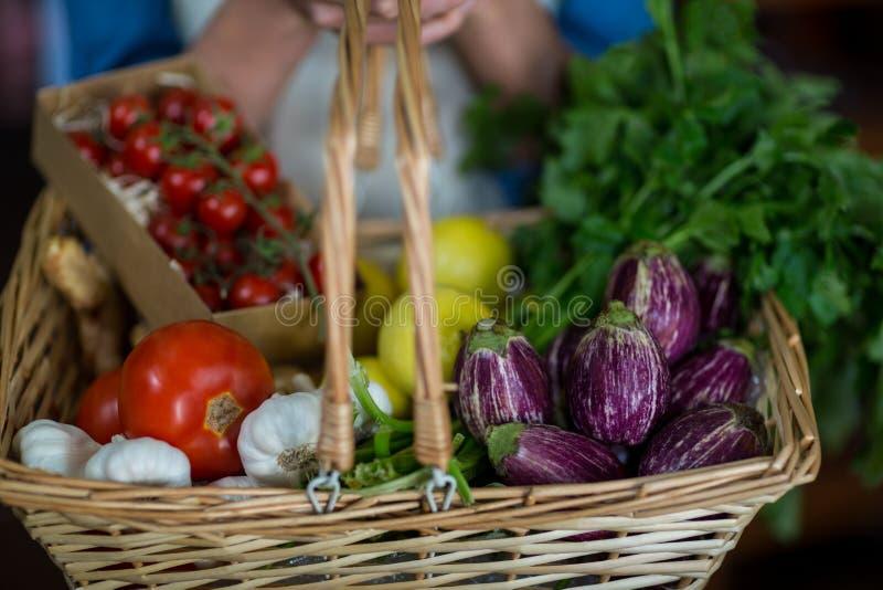 Close-up van de vrouwelijke mand van de personeelsholding van groenten in organische sectie stock afbeeldingen