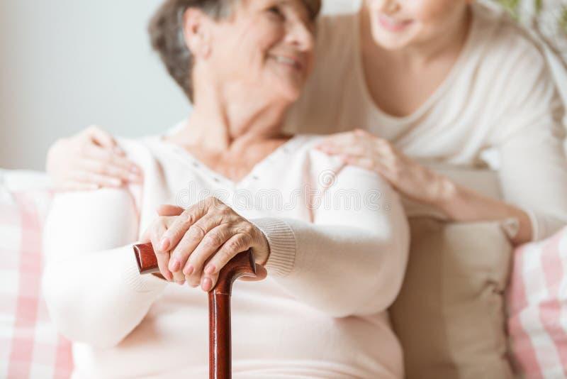 Close-up van de wandelstok van de bejaardeholding in de verzorging h royalty-vrije stock afbeeldingen