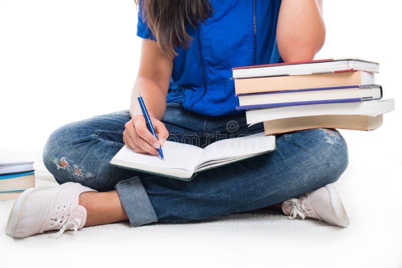 Close-up van de zitting die van het studentenmeisje in notitieboekje schrijven stock afbeelding