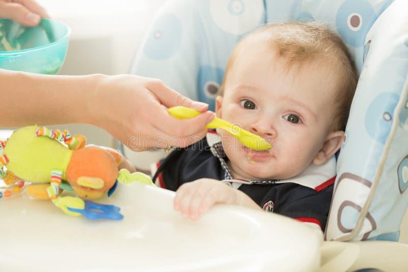 Close-up van de zitting van de babyjongen achter lijst bij highchair en het eten royalty-vrije stock afbeeldingen