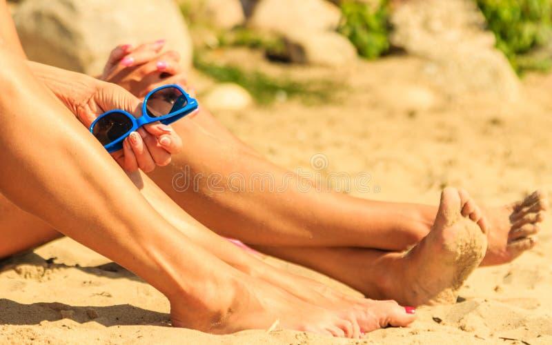 Close-up van de zon van vrouwenbenen het looien op strand stock foto's
