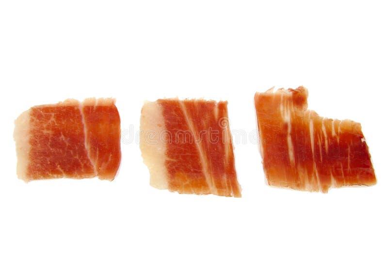 Close-up van drie geïsoleerde plakken van de serranoham stock foto