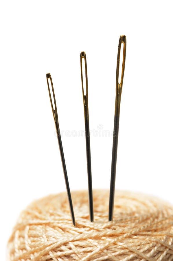 Close-up van drie naalden in clew die op wit wordt geïsoleerdo stock afbeeldingen
