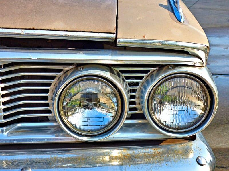 Close-up van dubbele koplampen op een klassieke auto stock foto's