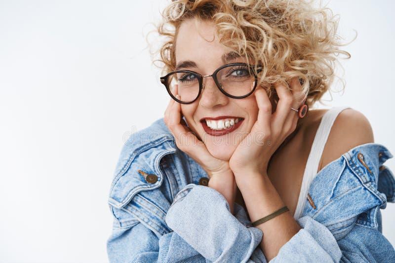 Close-up van dwaze romantische en mooie Europese vrouwelijke student in glazen en denimjasje wordt die lipctick het leunen dragen stock foto