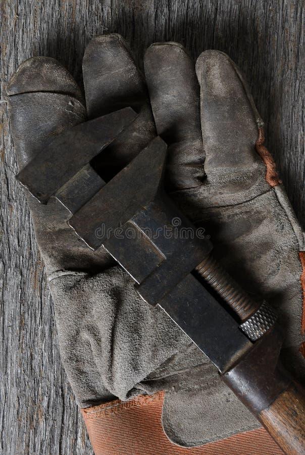 Close-up van een antieke moersleutel op een oude vuile het werkhandschoen royalty-vrije stock foto's