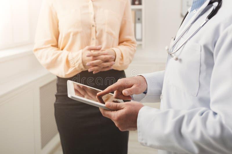 Close-up van een arts die in tablet en patiënt richten stock afbeeldingen