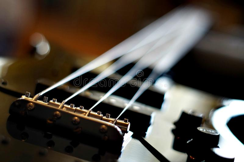 Close-up van een basgitaarbrug wordt geschoten - de stijlbrug die van Stootkussenjazz bass stock fotografie