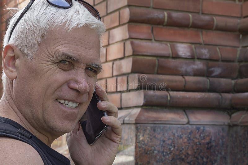 Close-up van een bejaarde die op een mobiele telefoon spreken stock afbeeldingen