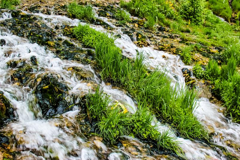 Close-up van een bergstroom met groen gras royalty-vrije stock afbeelding