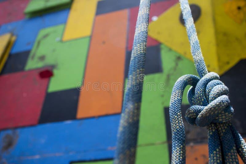 Close-up van een blauwe het beklimmen knoop die voor een kleurrijke gymnastiek hangen die muur beklimmen stock foto