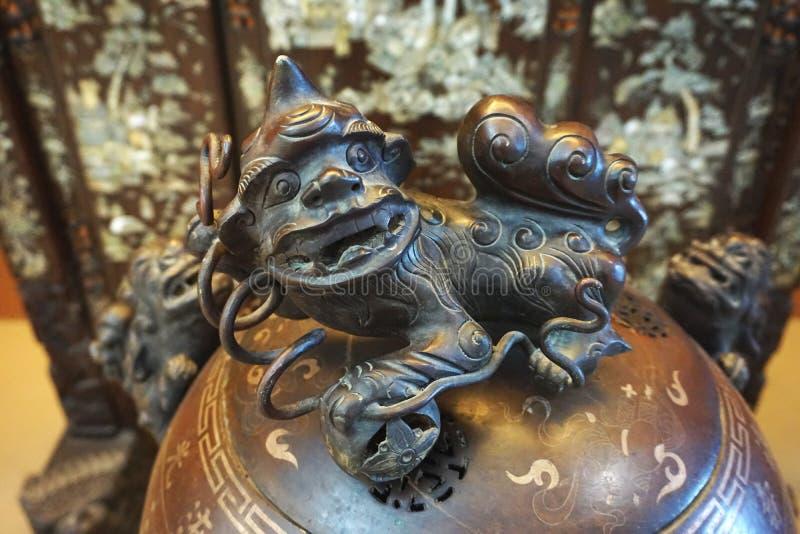 Close-up van een cijfer van de het demonbeschermer van het gietvormbrons boven op een oude urn in Zuidoost-Azië stock foto's