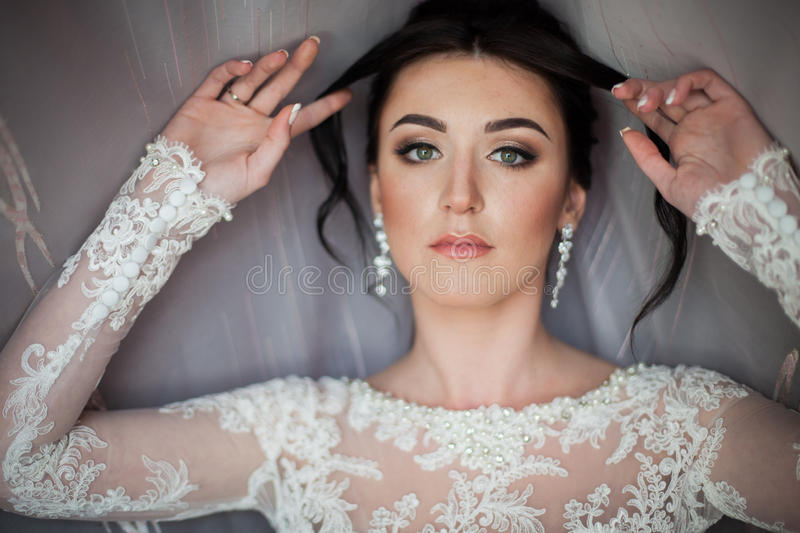 Close-up van een elegante, donkerbruine bruid in uitstekende witte dres wordt geschoten die stock afbeelding