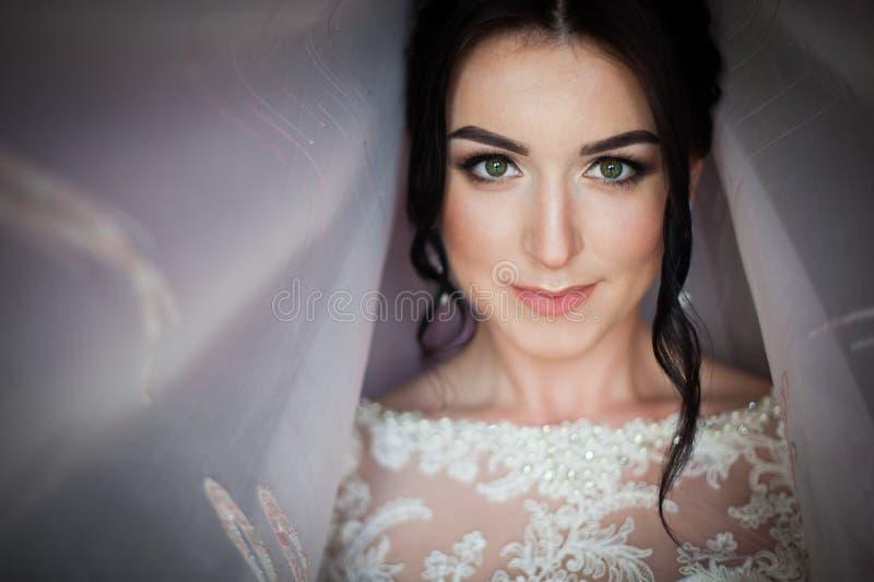 Close-up van een elegante, donkerbruine bruid in uitstekende witte dres wordt geschoten die stock foto's