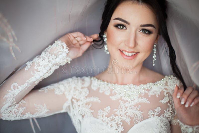 Close-up van een elegante, donkerbruine bruid in uitstekende witte dres wordt geschoten die royalty-vrije stock afbeelding