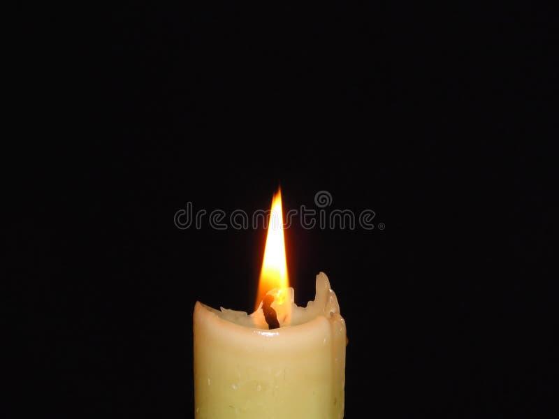 Close-up van een geïsoleerde brandende kaars op donkere zwarte achtergrond Vlam, licht, kaarswas royalty-vrije stock afbeelding