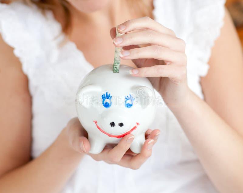 Close-up van een geld van de vrouwenbesparing in een piggy-bank stock foto