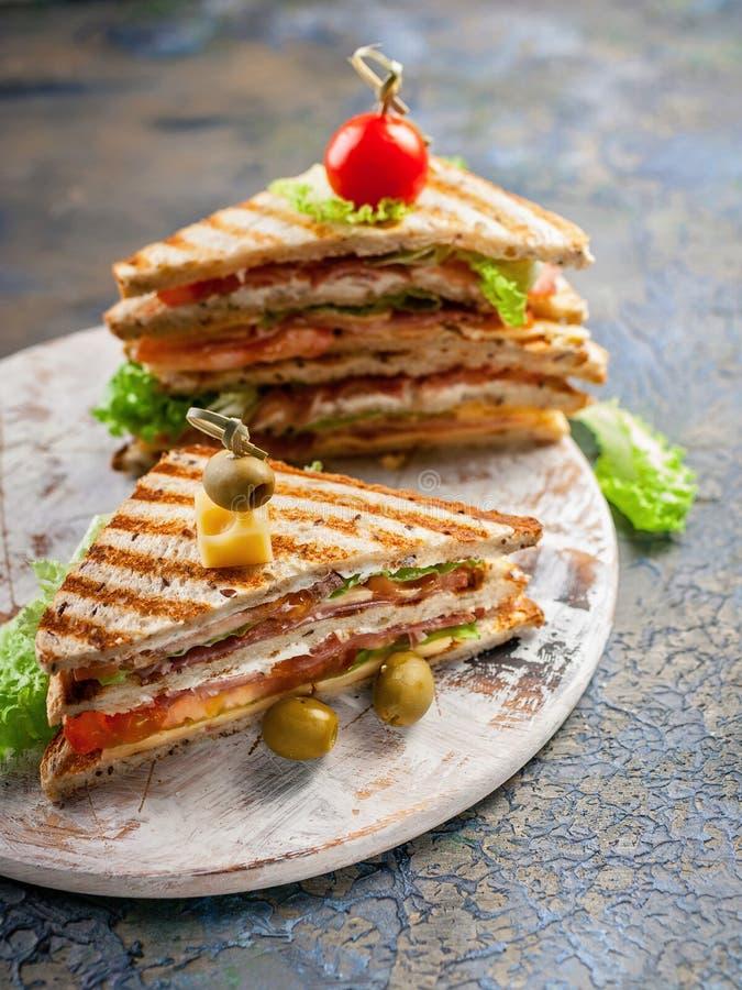 Close-up van een gerookte rundvleessandwich en een groene salade op een ronde scherpe raad Traditionele ontbijt of lunch Verticaa royalty-vrije stock afbeelding