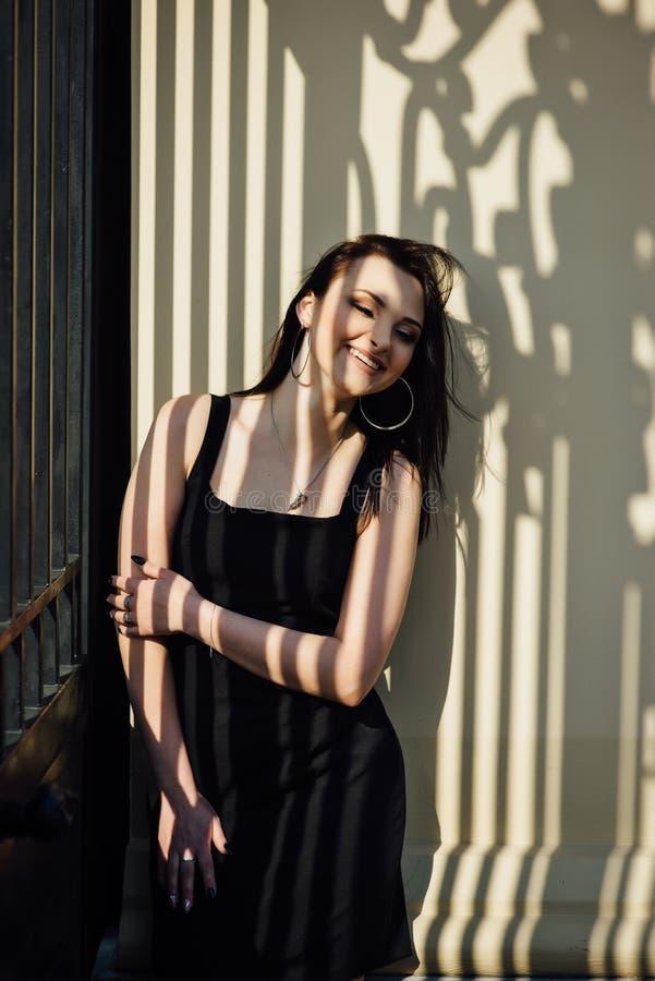 Close-up van een gezicht van een jong meisje dat en een schaduw van een metaalrooster op haar gezicht glimlacht royalty-vrije stock foto's