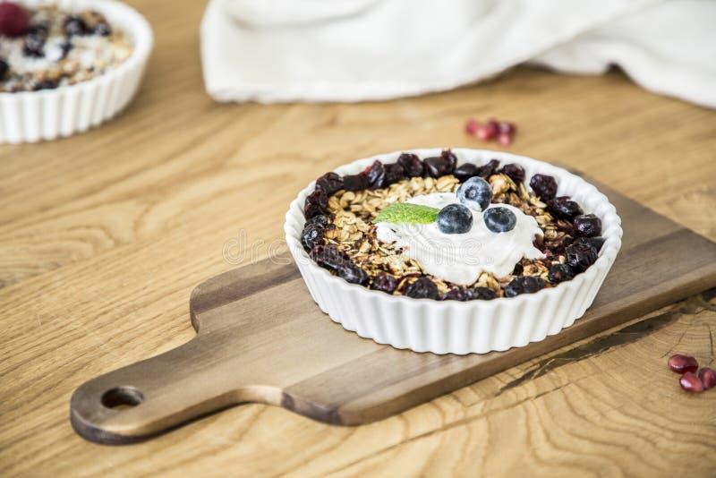 Close-up van een gezond ontbijt van havermeel en rozijnen met yogh stock afbeelding
