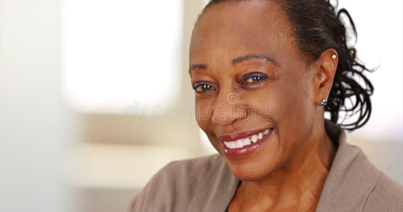 Close-up van een glimlachende bejaarde Afrikaanse Amerikaanse vrouw op het werk royalty-vrije stock fotografie
