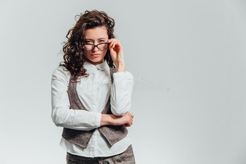 Close-up van een glimlachende donkerbruine bedrijfsvrouw die in glazen camera over witte achtergrond bekijken stock afbeeldingen