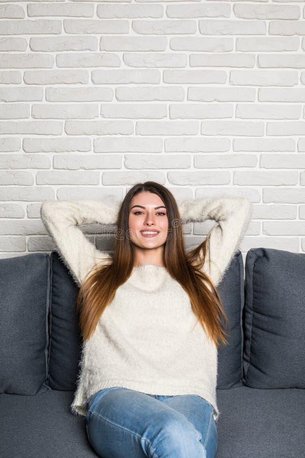 Close-up van een glimlachende jonge vrouw die op laag thuis liggen stock afbeelding