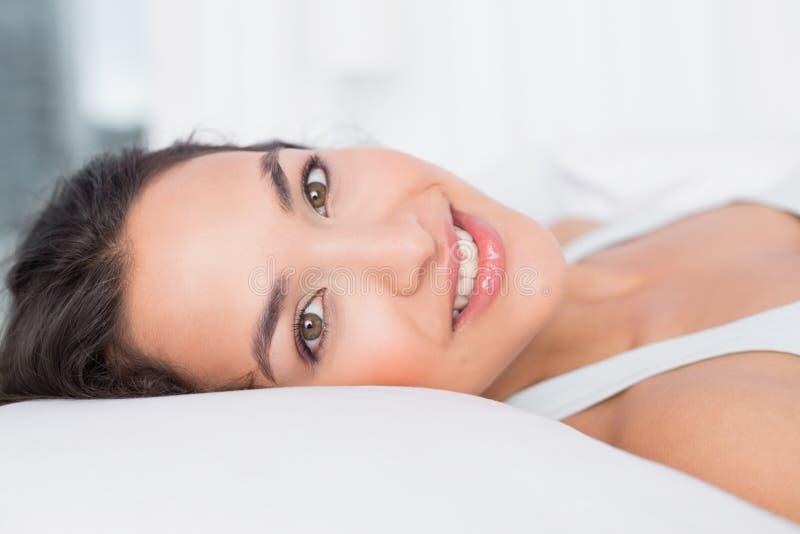 Close-up van een glimlachende mooie vrouw die in bed liggen stock afbeelding
