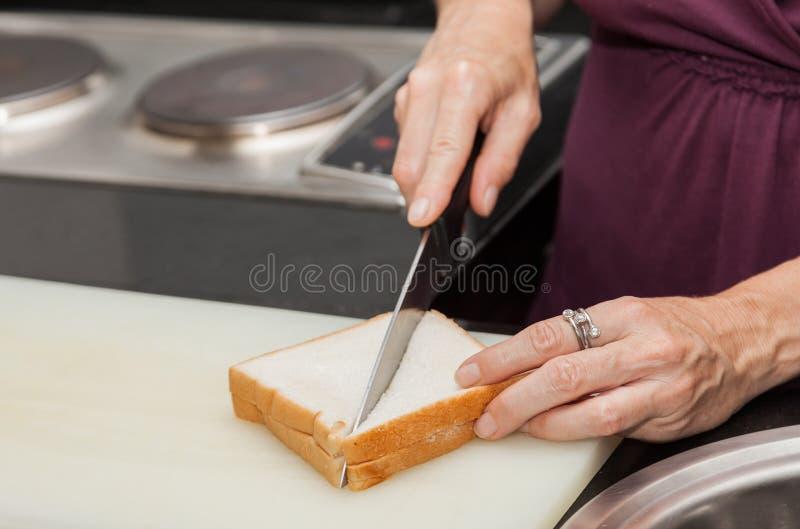 Close-up van een hand die een sandwich met het mes sneed royalty-vrije stock afbeeldingen