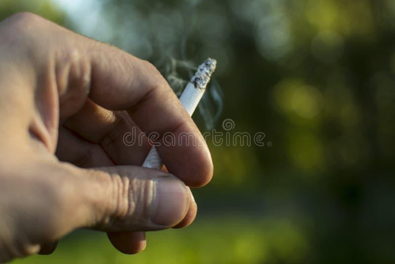 Close-up van een hand die een sigaret houden stock foto