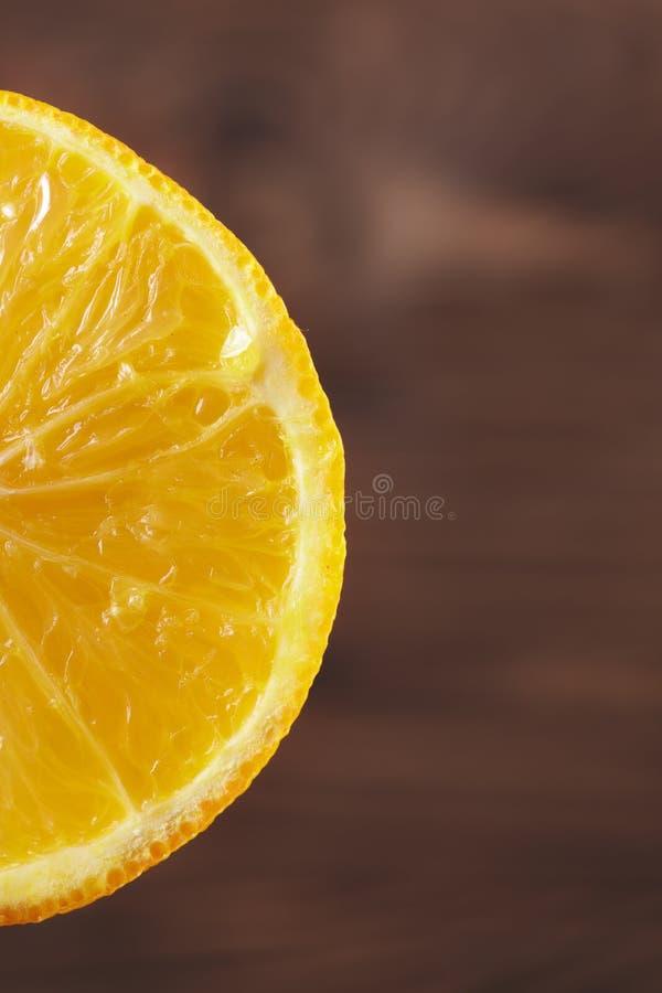 Close-up van een helder sappig succulent stuk van oranje, verse vruchten voor dranken op een bruine vage achtergrond stock foto's