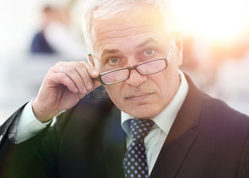 Close-up van een hogere zakenman die zijn glazen aanpassen royalty-vrije stock fotografie